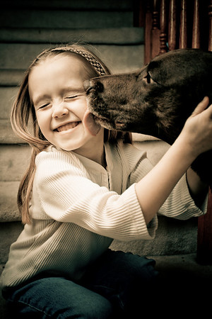Pretty dog licking a cute child's face