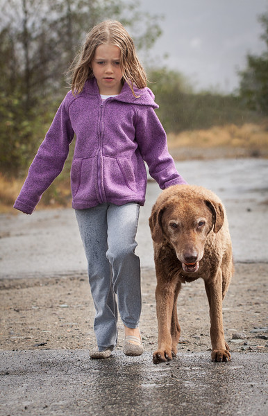 Child and old dog walking together